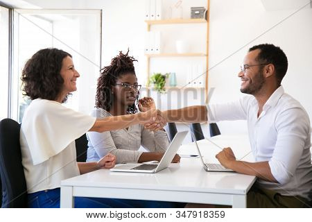 Cheerful business partners shaking hands. Confident young people reaching agreement. Agreement concept stock photo