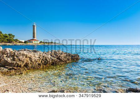 Croatia, Adriatic sea coastline, island of Dugi Otok, old lighthouse of Veli Rat on the stone shore, rocky shore in foreground stock photo