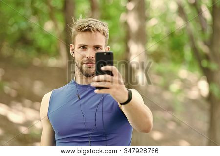 Create route run using application. Sportsman with smartphone and smart watch prepare for jog. Training with sport application is more fun. Man smartphone ready to start jog. Set up application. stock photo