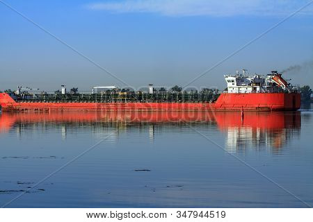 Large metal transport ship bulk carrier. A barge sailing with a cargo of containers from the port along the river. Sea transportation of cargo using dry cargo transport. stock photo