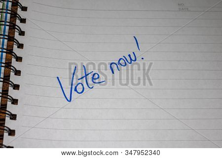 Vote now, handwriting  text on paper, political message. Political text on office agenda. Concept of democracy, voting, politics. Copy space. stock photo