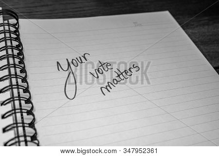 Your vote matters, handwriting  text on paper, political message. Political text on office agenda. Concept of democracy, voting, politics. Copy space. stock photo