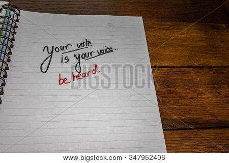 Your vote is your voice, handwriting  text on paper, political message. Political text on office agenda. Concept of democracy, voting, politics. Copy space. stock photo