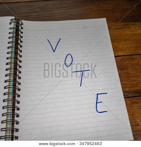 Vote, handwriting  text on paper, political message. Political text on office agenda. Concept of democracy, voting, politics. Copy space. stock photo