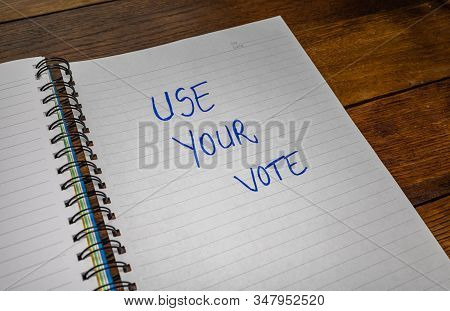 Use your vote, handwriting  text on paper, political message. Political text on office agenda. Concept of democracy, voting, politics. Copy space. stock photo