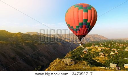 Beautiful hot air balloon flying over mountain village, Armenia aerial view stock photo