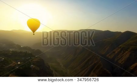 Aerial view of hot air balloon flying over mountain village at beautiful sunset stock photo