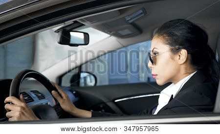 Confident female in business suit sitting in car national security agent on duty stock photo