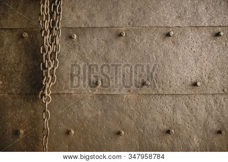 Metal rusty chain on the background of a metal rusty surface with bolt caps. Rough metal antique wall. stock photo