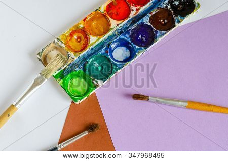 Set of used watercolor paints and brushes for painting. Accessories for creativity on a multi-colored table. View from above. Selective focus. Without anyone. stock photo