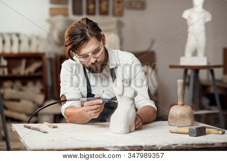Male sculptor repairing gypsum sculpture of womans head at the working place in the creative artistic studio. stock photo
