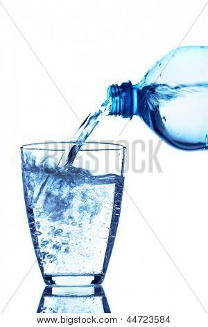 from a water bottle of water being poured into a glass stock photo