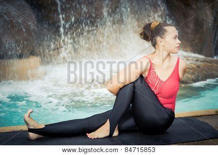 Woman practicing yoga near waterfall. Sage Twist. Marichyasana stock photo