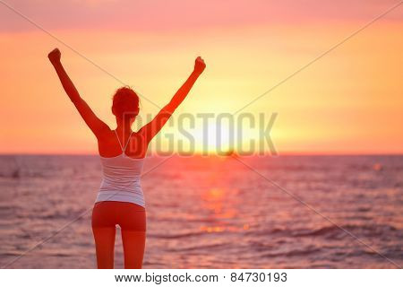 Happy cheering celebrating success woman at beautiful beach sunset. Fitness girl enjoying view with