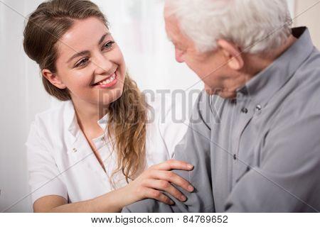 Smiling Nurse Assisting Senior Man