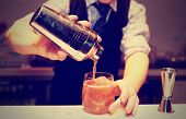 Bartender is making mixed drink at bar counter, conditioned picture