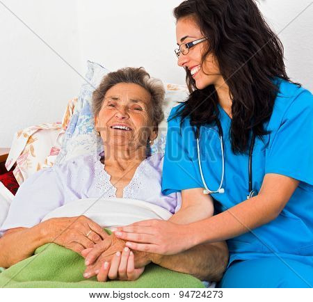 Kind nurse easing elderly lady's days in nursing home with care help and joy. stock photo
