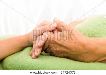 Health care nurse caring for elderly concept - holding hands. stock photo