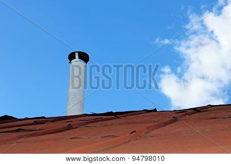Chimney pipe over the old tinny roof against the blue sky stock photo