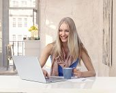 Happy youthful blonde easygoing caucasian lady working with portable PC phone retro home. Sitting at