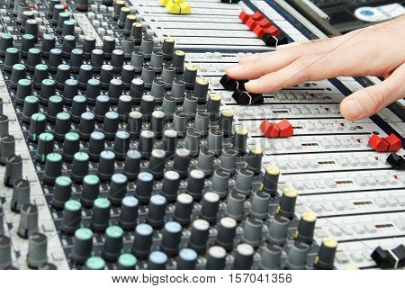 Soundman's palm and microphone on sound mixer background. Music instruments or dj concept. Musical equipment microphone with control console. stock photo