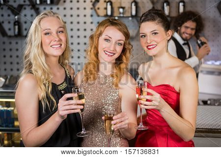 Portrait of three smiling friend having glass of champagne at bar stock photo