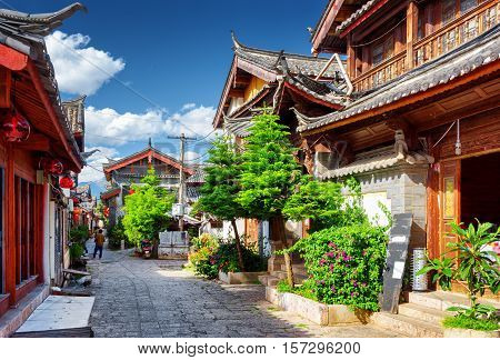 Scenic street in the Old Town of Lijiang Yunnan province China. Wooden facades of traditional Chinese houses. The Old Town of Lijiang is a popular tourist destination of Asia. stock photo