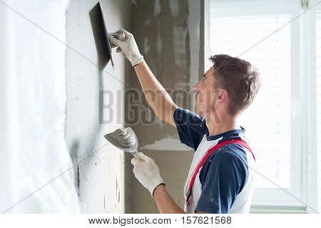Thirty years old manual worker with wall plastering tools renovating house. Plasterer renovating indoor walls and ceilings with float and plaster. stock photo
