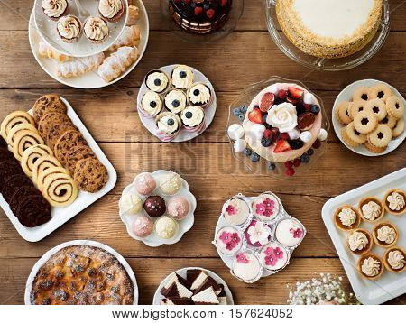 Table with cake, pies, cupcakes, tarts and cakepops. Studio shot on brown wooden background. Flat lay. stock photo