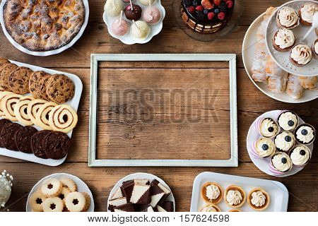 Table with picture frame, cakes, cupcakes, cookies, pie, tarts and cakepops. Studio shot on brown wooden background. Copy space. Flat lay. stock photo