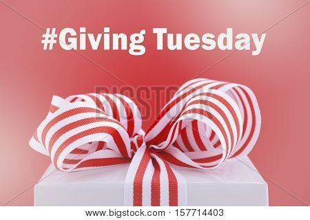 Red and white gift symbolic for Giving Tuesday with sample text on bright red and white background with applied faded filters. stock photo