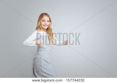 Tastes great. Pleasant content little girl smiling and thumbing up while being involved in cooking stock photo