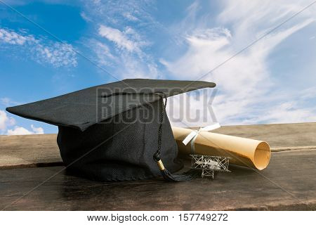 graduation cap hat with degree paper on wood table sky background Empty ready for your product display or montage. stock photo