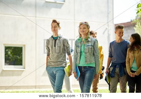 education, high school, communication and people concept - group of happy teenage students walking o