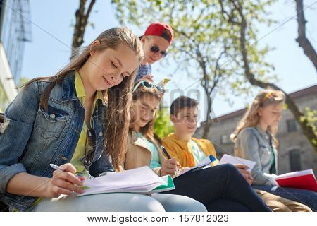 education, high school and people concept - group of teenage students with notebooks learning at cam