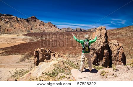 tourist man with opened arms at the Liano de Ucanca mountains Tenerife Canary Islands Spain stock photo