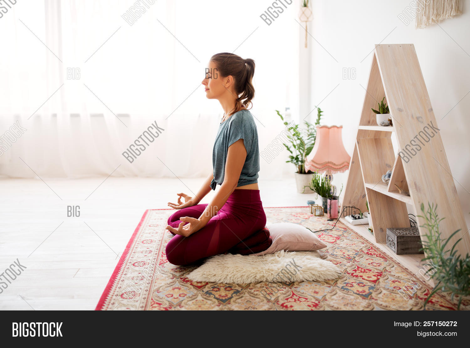 mindfulness, spirituality and healthy lifestyle concept - woman meditating in lotus pose at yoga stu