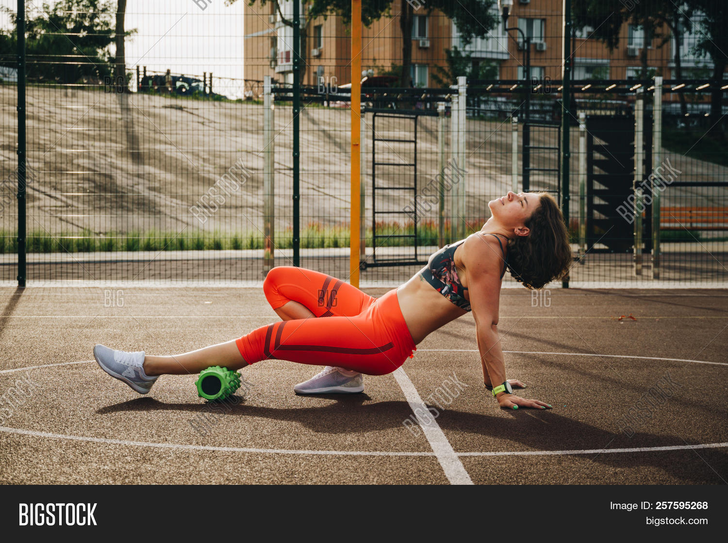 theme sport and rehabilitation sports medicine. Beautiful strong slender Caucasian woman athlete uses foam roller green field street workout to workout to remove pain, stretch and massage muscles