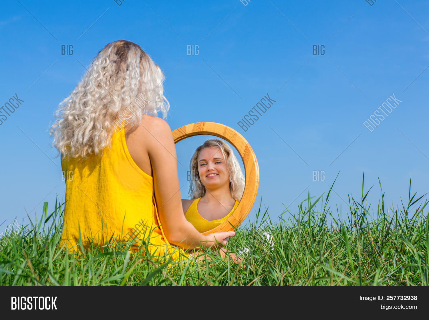 Blond woman sits looking at her mirror image outside