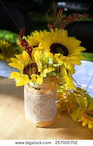 Jar covered in burlap and lace filled with faux sunflowers set on an outdoor table covered with burlap and white fabric stock photo