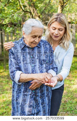 Disabled old lady taking medical pills from friendly carer's hand. Spending time in the garden stock photo