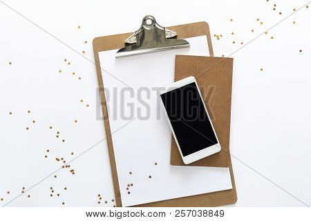Top view over the working desk with paper, notebook and phone at the top with randomly droped golden stars. Copy space for text. Flat lay of a workplace on white background stock photo