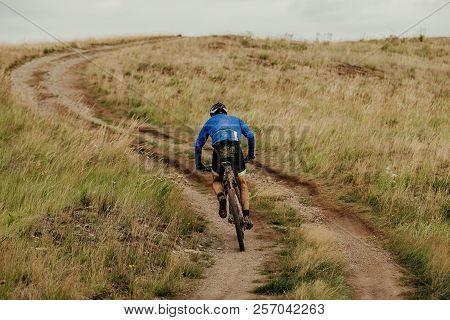 back male cyclist climbing uphill on mountain bike trail stock photo