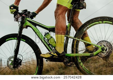 dirty feet athlete cyclist rides on mountainbike with water bottle stock photo