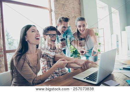 Four cheerful people, friends,  enjoying funny video tutorial, guys and girls pointing with fingers at screen of netbook at light interior room, gathering stock photo