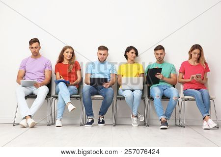 Group of young people waiting for job interview near light wall stock photo
