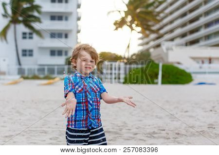 Portrait of happy little kid boy on the beach of ocean. Funny cute child making vacations and enjoying summer. Blond preschool child on beach of Miami, Florida, USA on stormy day stock photo