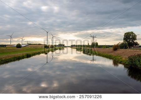 Wind turbines and high voltage pylons reflected in the mirror smooth water surface. Solar panels for generating electricity can also be seen in the background. It is a cloudy day in the Dutch summer. stock photo