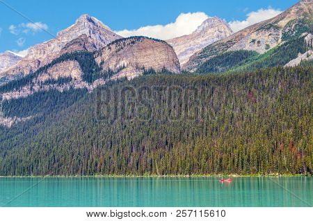 A lone red canoe on turquoise colored Lake Louise in Banff National Park with Mount Whyte, Beehive Mountain and Mount Niblock in the background. stock photo
