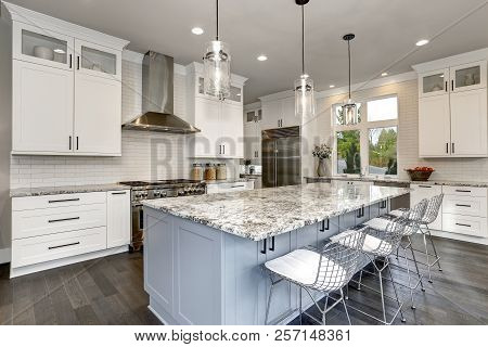 Beautiful Kitchen In Luxury Home Interior With Island And Stainless Steel Chairs